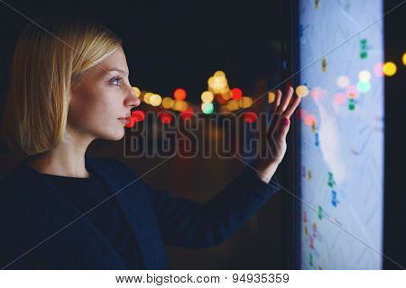 Young beautiful female tourist using smart city gadget to get direction in Barcelona central
