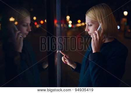 Beautiful woman verifies account balance on banking application while standing in night city