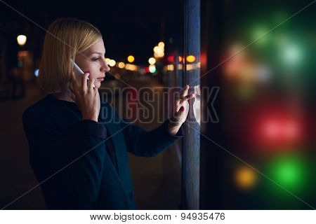 Young caucasian woman talking on cellphone touching sensitive screen of smart city bus stop