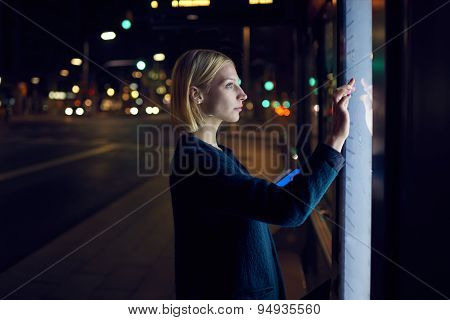 Female caucasian tourist touching information kiosk digital screen while standing outdoors