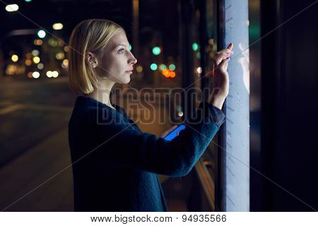 Gorgeous young woman touching big digital screen while consults about touristic information
