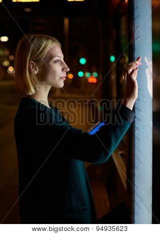 Caucasian female using automated teller machine with big digital screen while standing in night city