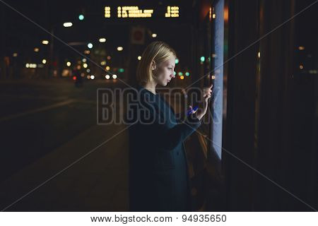 Pretty woman touching big digital screen of smart bus station while standing in beautiful night city