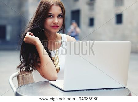 Attractive young woman sitting at sidewalk cafe table with open netbook next to her