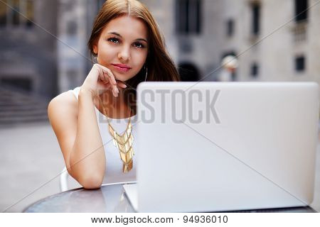Beautiful young female read digital book on laptop computer while sitting in sidewalk cafe
