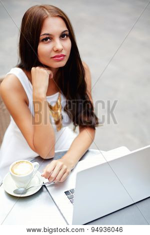 Female freelancer drinking coffee while sitting with open laptop computer outdoors