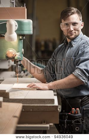 Woodworker Using Drilling Machine