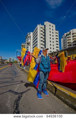 Street vendor selling ecuadorian flags for protesters marching in the capital city Quito against gov