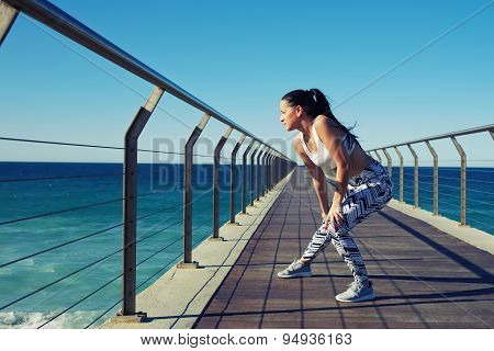 Female runner warming up before her daily exercise routine on the beach enjoying nature