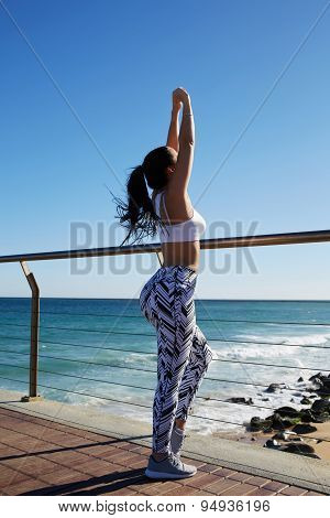 Young fit woman with beautiful figure stretching her arms out before a workout outdoors