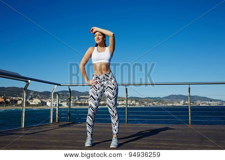 Beautiful young woman relaxing after long jog by the beach while standing on wooden jetty