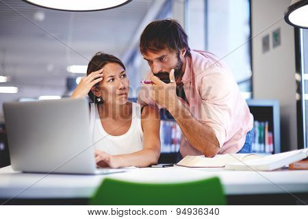 Two office workers talking in an office interior while discussing work on a laptop computer