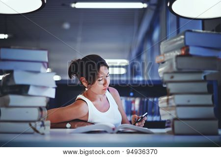 Asian female student sitting at the desk behind stack of book looking exhausted and tired to study