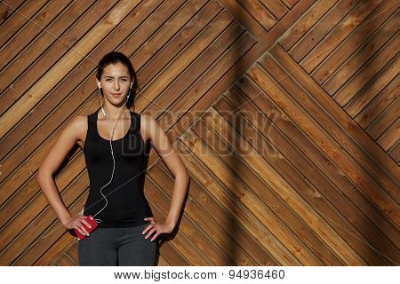 Young woman in sportswear listening to music with her headphones while standing on wooden background