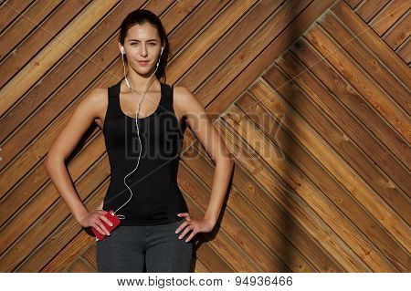 Sporty young girl listening to music while standing near the wooden wall with big copy space
