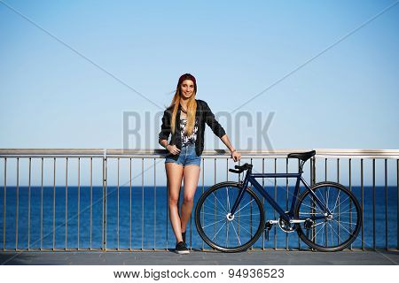 Young woman standing on the pier before ride along the seaside on her bicycle at sunny day