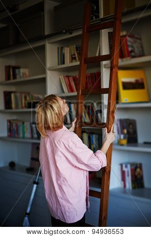 Businesswoman in book apartment cabinet searching  some book from the shelf of home book collection