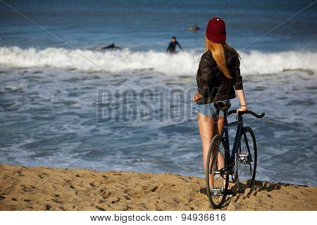 Attractive young hipster girl standing on seashore looking to surfing people in water