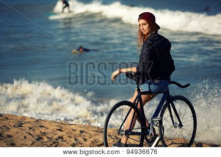 Attractive young hipster girl relaxing on the beach after ride on her sport fixed gear bicycle