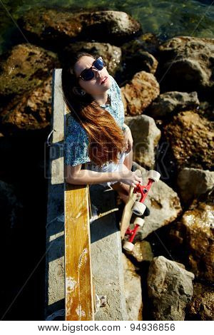Cool young woman posing with her skateboard in front of the sea while enjoying summer sunshine