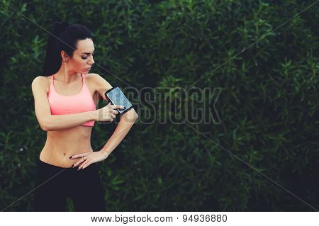 Sporty young woman standing in the park with big copy space for text while getting ready for workout