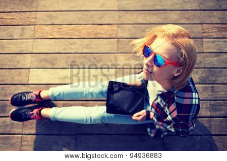 Girl with blonde hair in summer colorful glasses using digital tablet while sitting on a wooden pier