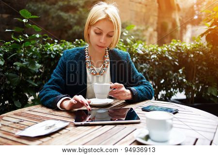 Young female at coffee time working on digital tablet while sitting on the terrace of coffee shop