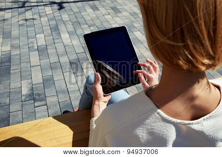 Rear view female student using touchpad with blank screen outdoors in urban setting