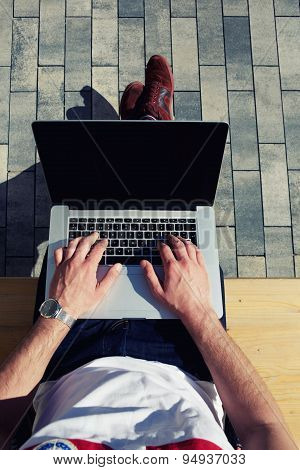 Male hands using notebook with black screen outdoors in urban setting while typing on keyboard