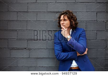 Concentrated business man standing with arm crossed and hand against his mouth looking pensive