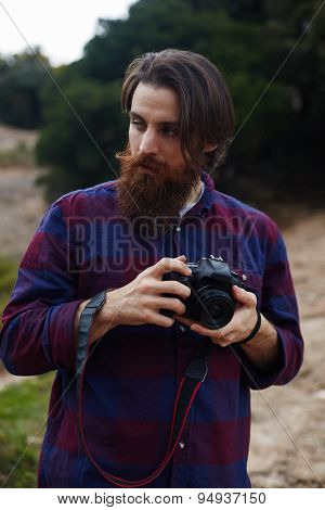 Handsome hipster tourist checking out the sights in nature landscape holding his professional camera