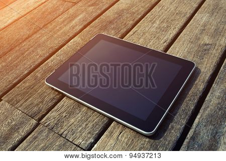 Black digital tablet with blank screen for your text message lying on wooden floor