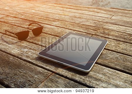 Touchpad wireless device and sunglases lying on wooden jetty at sunny day