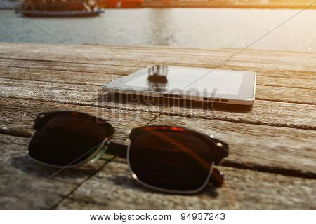 Sunglases and digital tablet lying on wooden jetty with sailing tourist boat on background