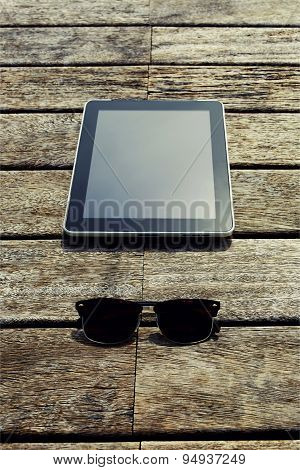 Top view mock up presentation of digital tablet and sunglases lying on wooden jetty at sunny day