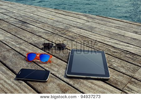 Top view mock up presentation with blank screen digital tablet smart phone and couple of sunglases