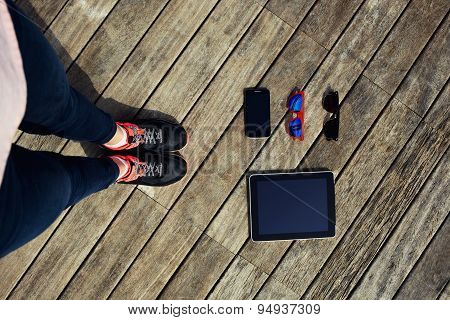 Female legs standing on wooden floor with everyday objects lying on the wooden pier