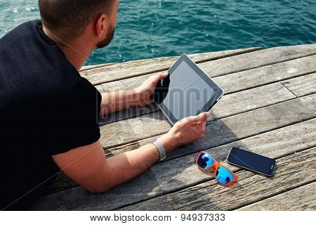 Young man using digital tablet while lying on wooden jetty at marina port during his vacation