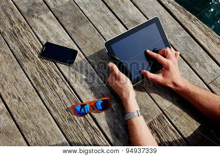 Top view male hands using digital tablet on wooden jetty background vacation holidays