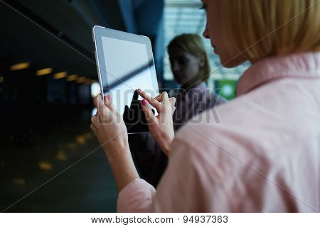 Side view young businesswoman using her wireless devices in modern office
