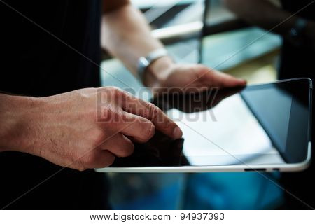 Businessman using his wireless devices during a meeting work on a tablet screen
