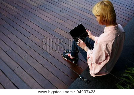Hipster woman using touchscreen device with big copy space while sitting on a wooden floor