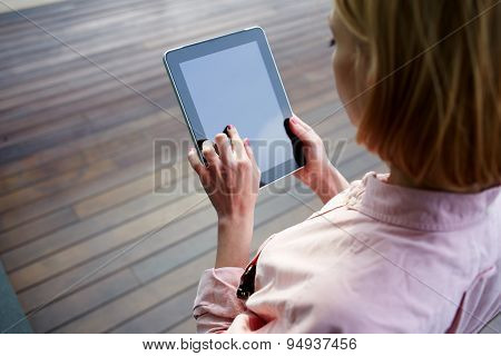 Close up female student hands using blank screen touchpad against wooden background