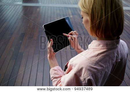Freelancer girl working on her digital tablet with big copy space against wooden background