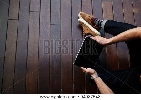 Modern successful businessman working on his touchpad while sitting on wooden floor