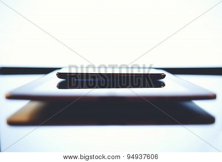 Close up shot with smart phone above digital tablet lying on glass modern desk