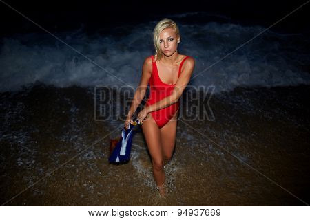 Charming caucasian girl with beautiful figure standing on the beach while enjoying ocean night
