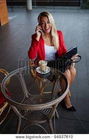 Young woman speaking on a cellphone at a cafe  during her lunch break in a coffee shop