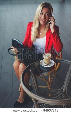 Attractive businesswoman talking on mobile phone during her lunch break in a coffee shop
