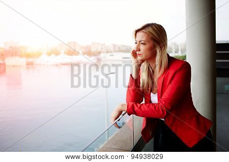 Pensive businesswoman looking out of an office balcony with beautiful seaport view on background